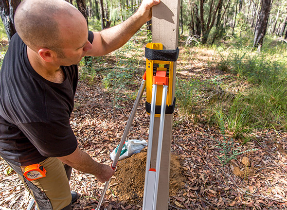 Using the two bubbles on the post levelling device to make sure the post is level.